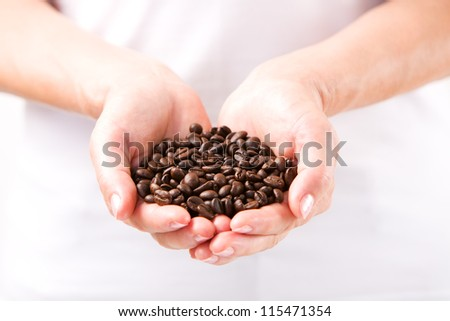 Coffee beans in female hands - stock photo