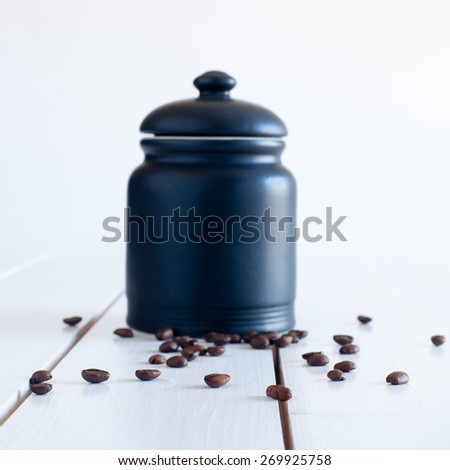 coffee beans in front of a black jar of china - stock photo