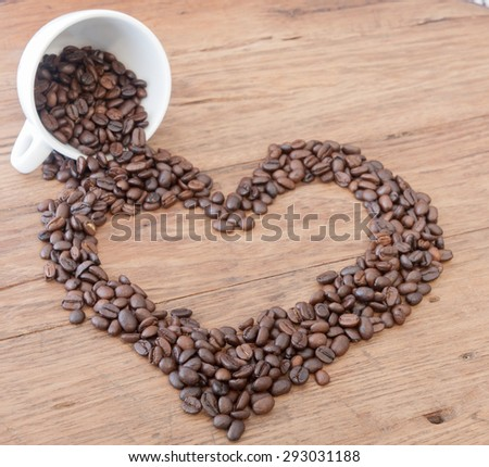 Coffee beans in heart shape on wood table - stock photo