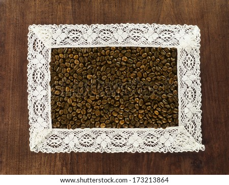 coffee beans in lacy crochet frame on wooden background - stock photo