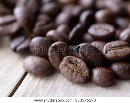 Coffee beans in natural light on a wooden board texture macro - stock photo