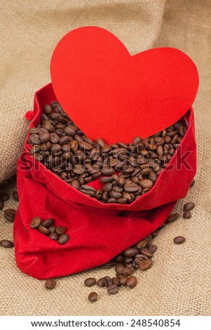Coffee beans in red velvet sac with red paper heart - stock photo