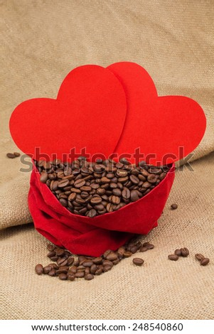 Coffee beans in red velvet sac with two red paper hearts - stock photo