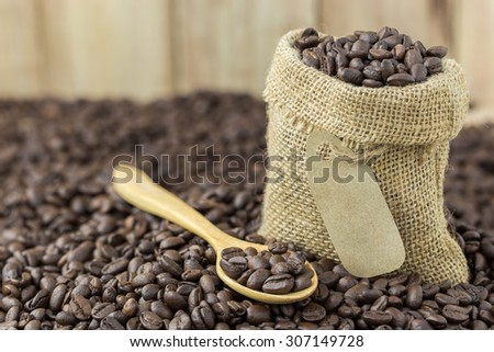 coffee beans in sack bag and spoon on roasted coffee seed background - stock photo