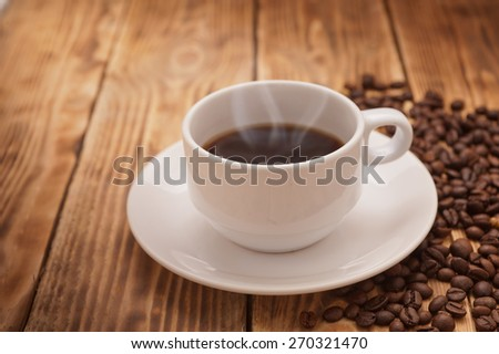 Coffee beans in sack on a wooden table - stock photo