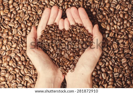 Coffee beans in the hands of heart shaped - stock photo