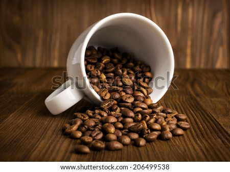 coffee beans in white cup close-up on wooden - stock photo