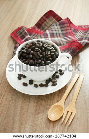 Coffee beans in white cup on wood table and a couple of wood cutlery and tablecloth plaid red brown. - stock photo