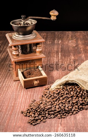 Coffee beans ly spilled from a hessian bag on a wooden table with an old grinder in the back. - stock photo