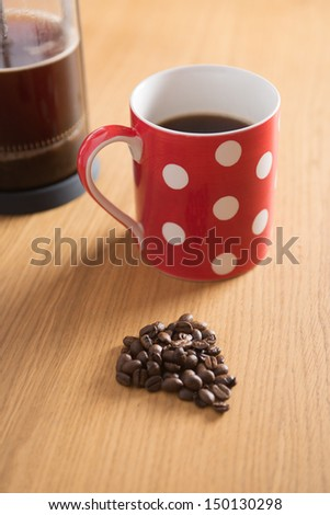 Coffee beans on a wooden table with a freshly brewed cafetiere and red spotty cup in the background - stock photo