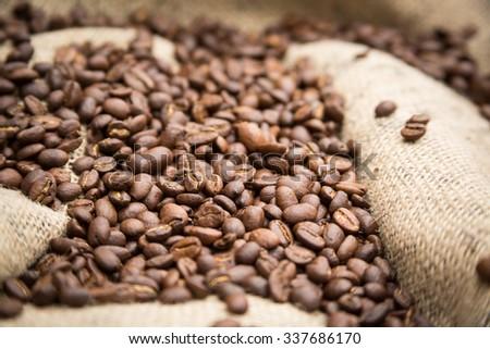 Coffee beans on burlap sack - stock photo