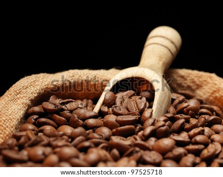 Coffee beans on burlap sack with wooden scoop - stock photo