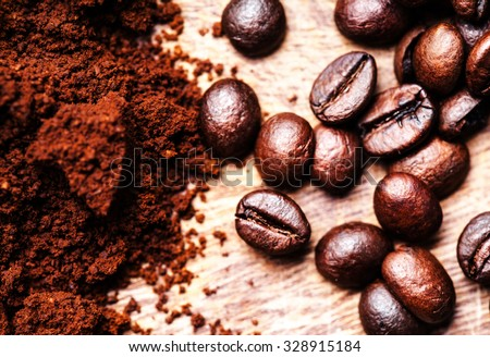Coffee beans on macro ground coffee background, top view image. Arabic roasting coffee - ingredient of hot beverage close up - stock photo