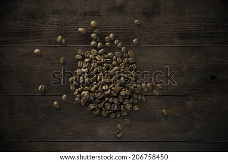 Coffee beans on old wooden texture - stock photo