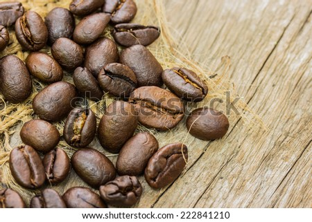 Coffee beans on sacking and wood background
