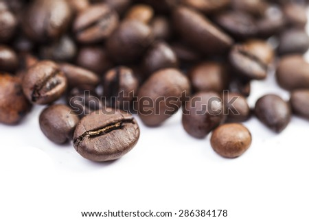 Coffee beans on white background with shallow depth of field - stock photo