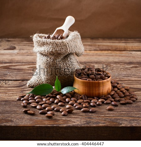Coffee beans on wood background, coffee beans in bag and green leaf.
