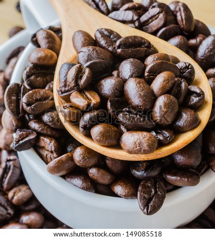 Coffee beans on wood spoon - stock photo