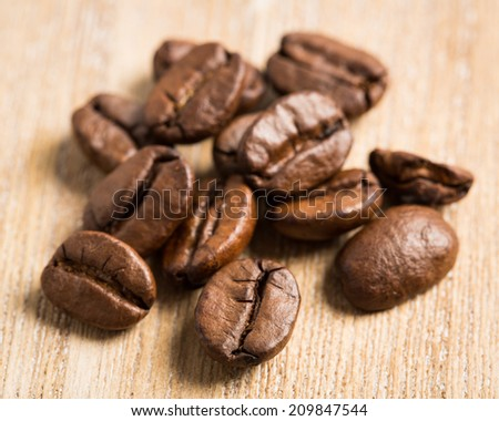 Coffee beans on wooden board - stock photo