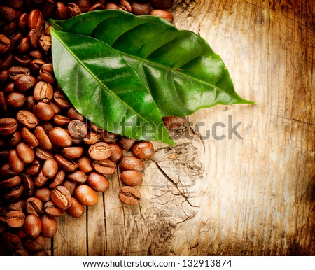 Coffee Beans over Wood Background. Beans And Leaf on Wooden Table - stock photo