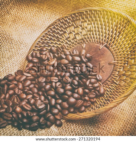 Coffee beans poured from wicker lid on burlap, instagram effect - stock photo