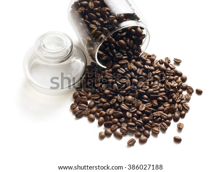 Coffee beans pouring out from a glass container, isolated on white background.  - stock photo