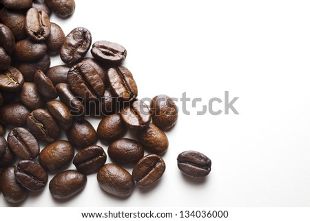 coffee beans spilled from left to right on a white background, copy space - stock photo