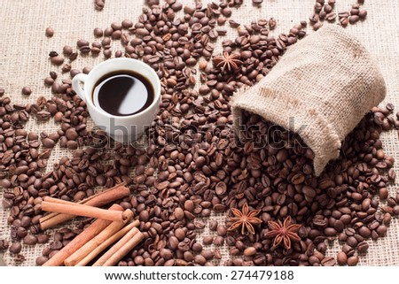 Coffee beans spilled out of the bag on the fabric in the photo have cinnamon sticks and star anise. Cinnamon is an angle of 45 degrees to the center of the frame in the lower left corner,  - stock photo