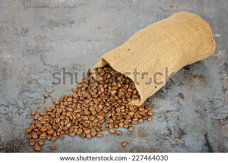 Coffee beans spilled out of the sack - stock photo