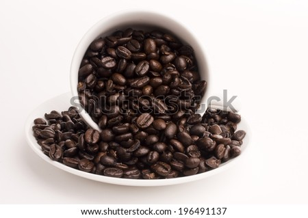 Coffee beans spilling from inside a white cup onto a saucer.