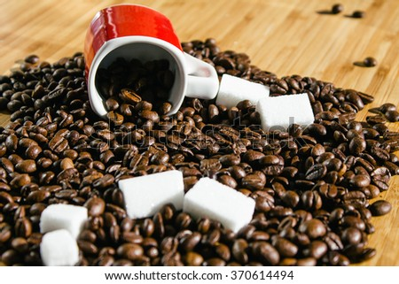 Coffee beans spilling out from a red cup and sugar cubes - stock photo