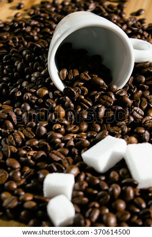 Coffee beans spilling out from a white cup and sugar cubes - stock photo