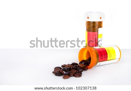 Coffee beans spilling out of a prescription bottle, isolated white background - stock photo