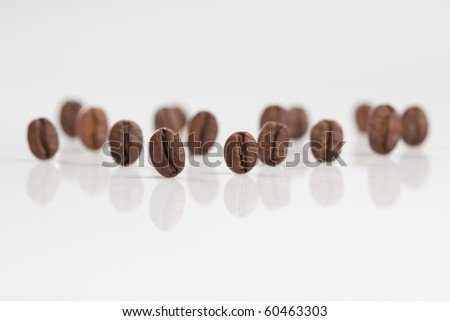 Coffee beans stand on reflecting white surface.