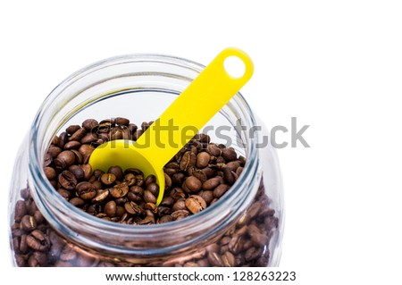 Coffee beans stored in a glass jar with scoop, white isolation.