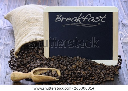 Coffee beans with blackboard on a wooden table. - stock photo