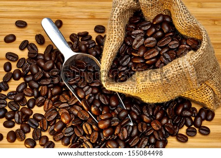 Coffee beans with burlap bag and scoop on wooden background under evening light - stock photo