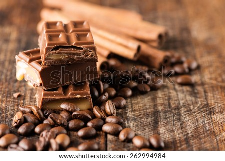 Coffee beans with chocolate candy bar on wooden table - stock photo