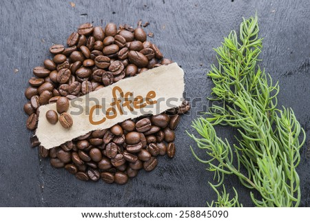 Coffee beans with Coffee text label on black wooden background. - stock photo
