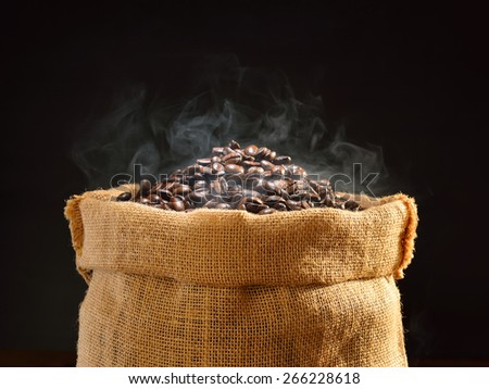 Coffee beans with smoke in burlap sack - stock photo