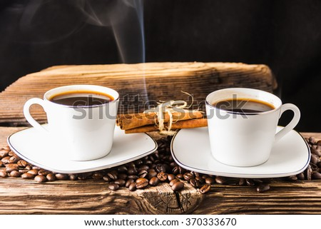 Coffee beans with smoke on wooden background