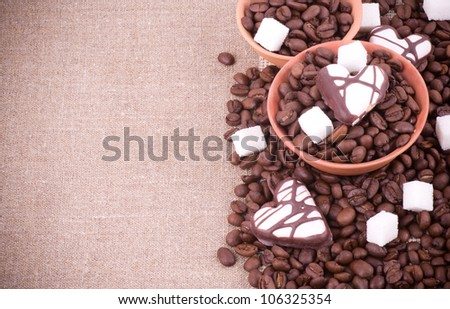 Coffee beans with sugar on sacking background - stock photo