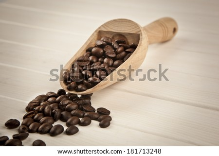 coffee beans with wooden spoon - stock photo