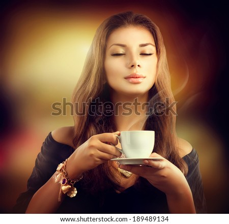 Coffee. Beautiful Woman Drinking Tea or Coffee in Cafe. Beauty Model Girl with the Cup of Hot Beverage. Warm Colors Toned  - stock photo