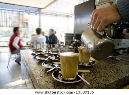 coffee being made at cafe with people in the background - stock photo