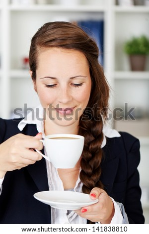 Coffee break at the office with a smiling young woman savoring the aroma of a freshly brewed cup of coffee - stock photo