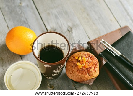 Coffee break at work. Take out coffee, cupcake, orange, notebooks and pen on wooden table  - stock photo