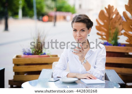 Coffee break. Attractive young businesswoman in formalwear smiling while sitting in sidewalk cafe and drinking coffee. - stock photo