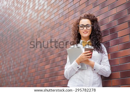 Coffee break. Attractive young woman holding cup of beverage and tablet computer against brick wall. - stock photo