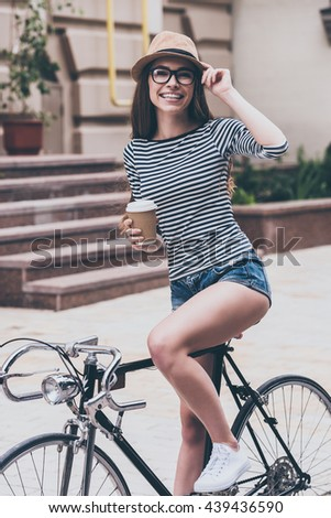 Coffee break before a ride.  Beautiful young woman holding coffee cup and leaning at her bicycle with smile while standing outdoors - stock photo